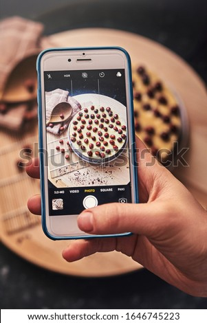 Taking a picture with a smartphone of a Homemade chocolate cake decorated with hazelnut and mascarpone cream. Aerial view with wooden spoon and kitchen towel background