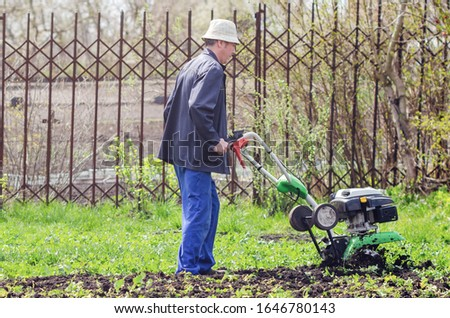 A man cultivates the land with a cultivator in a spring garden. #1646780143