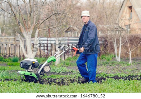 A man cultivates the land with a cultivator in a spring garden. #1646780152