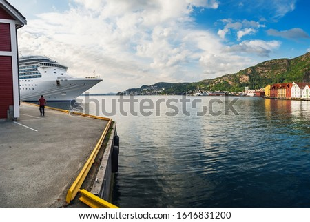 Cruise ship arrives at port in Bergen, Norway. Cruiseship liner in waters of Norwegian fjord, scenic summer panorama with the Old Town pier architecture