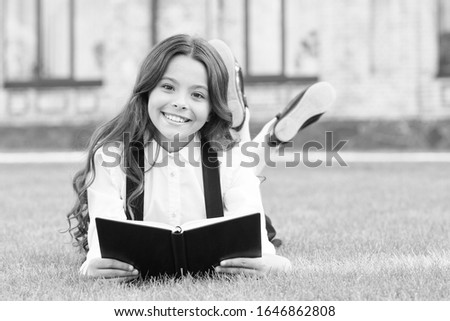 Her hobby is literature. Happy small child read childrens literature outdoor. Adorable little girl enjoy reading English literature at leisure. Learning foreign literature at school. #1646862808