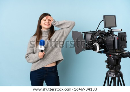 Young reporter woman holding a microphone and reporting news laughing #1646934133
