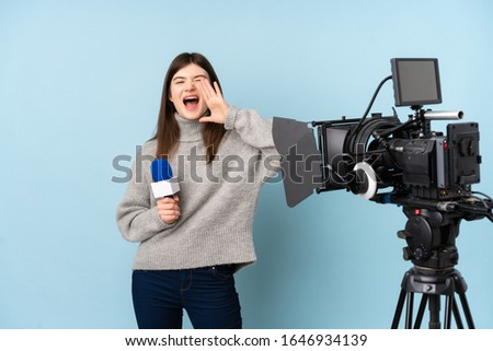 Young reporter woman holding a microphone and reporting news shouting with mouth wide open #1646934139