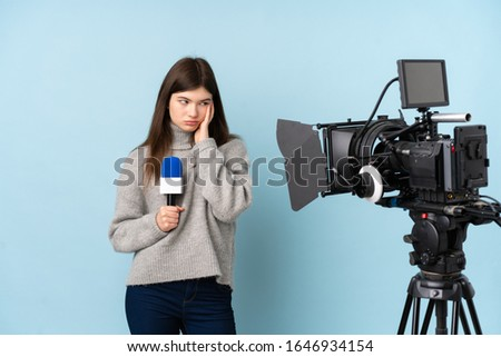 Young reporter woman holding a microphone and reporting news unhappy and frustrated #1646934154
