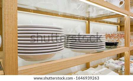 Furniture and kitchen utensils are for sale in a store. Beautiful and stylish home furnishings. Glass goblets, plates, cutlery. Modern furniture store interior decoration. #1646939263