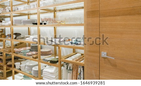Furniture and kitchen utensils are for sale in a store. Beautiful and stylish home furnishings. Glass goblets, plates, cutlery. Modern furniture store interior decoration. #1646939281