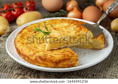 Spanish omelette with potatoes and onion, typical Spanish cuisine. Tortilla espanola. Rustic dark background. Top view #1646945236