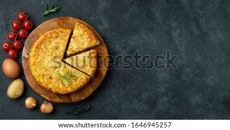 Spanish omelette with potatoes and onion, typical Spanish cuisine on a black concrete background. Tortilla espanola. Top view with copy space #1646945257