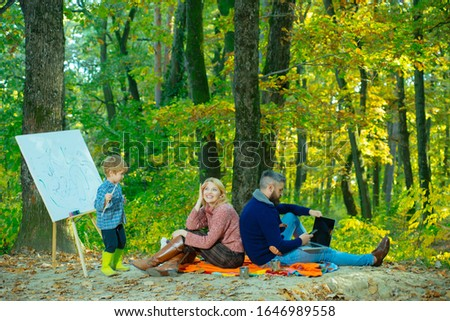 Surprised woman smile and looks up in the sky. Cheerful family sitting on the grass during a picnic in a autumnal park. A young family with small child having picnic in autumn nature at sunset