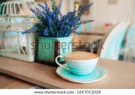 Cup of freshly brewed coffee with milk foam and a pattern in a turquoise-blue porcelain mug on a saucer against a background of violet flowers in a vase. Grab a coffee in the light interior of cafe. #1647012028