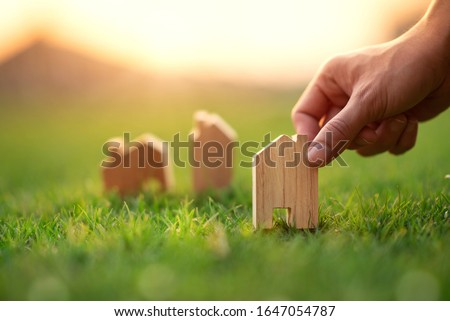 Hand of woman choosing mini wood house model on green grass, Planning buy Real Estate, eco house icon concept.