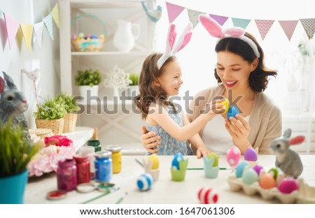 Happy easter! A mother and her daughter painting Easter eggs. Happy family preparing for Easter. Cute little child girl wearing bunny ears on Easter day. #1647061306
