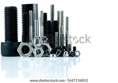Metal bolts and nuts on white background. Fasteners equipment. Hardware tools. Stud bolt, hex nuts, and hex head bolts in workshop. Threaded fastener use in automotive engineering. Hexagonal bolt. Royalty-Free Stock Photo #1647136852