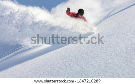 heliski snowboarding. freerider in a bright suit rides snowboarding with large splashes of snow on a sunny day. Young snowboarder. concept snowboard. big swirls of fresh snow in Good powder day #1647210289
