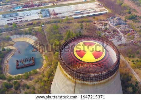 Chernobyl disaster. Radioactive zones near the reactor in Chernobyl. Sign of radiation on the background of the cooling tower in Chernobyl. Radiation contamination area near the Chernobyl reactor. #1647215371