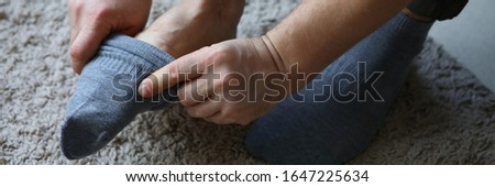 Man at home in morning puts gray socks on his leg. For a long time do not change clothes concept #1647225634