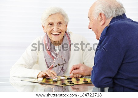 Happy senior couple playing checkers in a retirement home #164722718