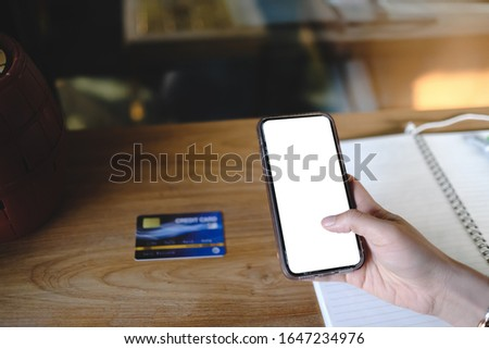 Close up of woman using cell phone with credit card sending massages and shopping online on the coffee shop with black screen,texting,video calls.