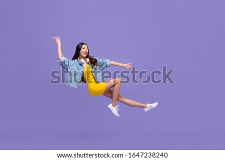 Young beautiful smiling Asian girl floating in mid-air with hand pointing up and down isolated on purple background #1647238240