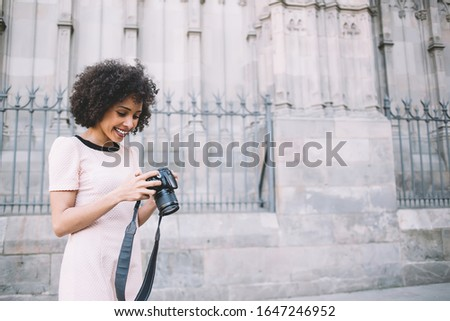Carefree female photographer with professional camera checking pictures for editing images, happy dark skinned woman with curly hair enjoying free time for practicing with skills of favorite hobby
