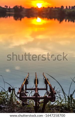 Fishing adventures, carp fishing. Angler, at sunset, is fishing with carpfishing technique. Camping on the shore of the lake.Carp Fishing Sunset #1647258700