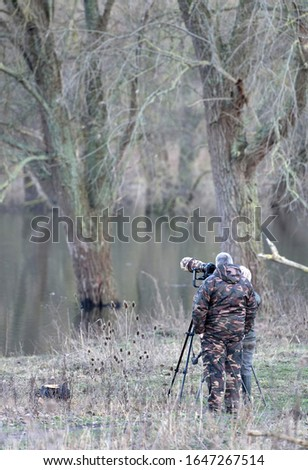 A man in camouflage suit is taking pictures with a camera on a tripod and a telelens covered in camouflage colours. Picture is low depth of field