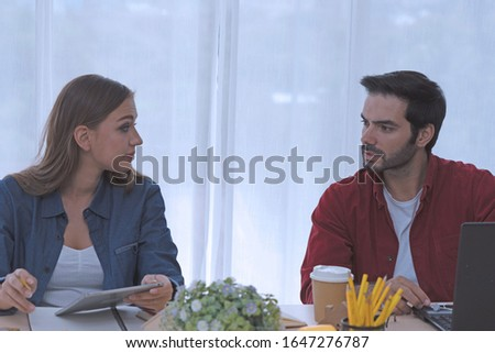 Caucasian man and Caucasian young woman are working at the coworking space. They are communicating together with happy mood. The room has white background. top half of body compisition. #1647276787