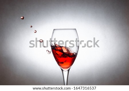 Glass with splashes, drops of red wine on a white background. Freezing liquids in motion #1647316537