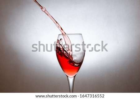 glass of red wine on a white background. Freezing the movement of liquids in the photo. #1647316552