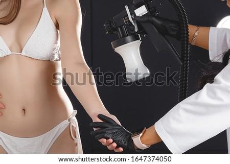 Beauty master applying fake tan on woman`s body. Ekotanning. Ecological tan. Female making tanning in tan studio. Client making an express bronzing by airbrush-pistol. #1647374050