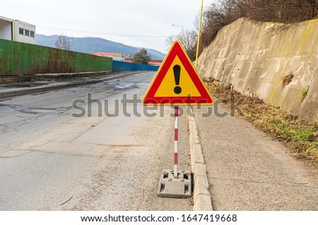 road traffic sign watch out for danger on asphalt road damaged roadway delay traffic