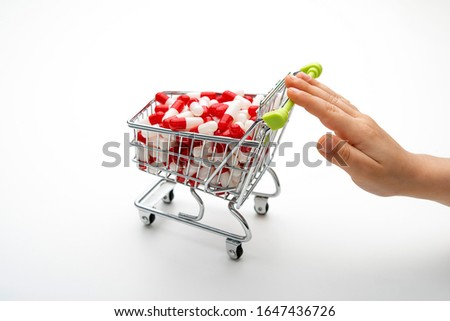 shopping cart full of medicines pushed by a child's hand, concept of addiction to the use of drugs #1647436726
