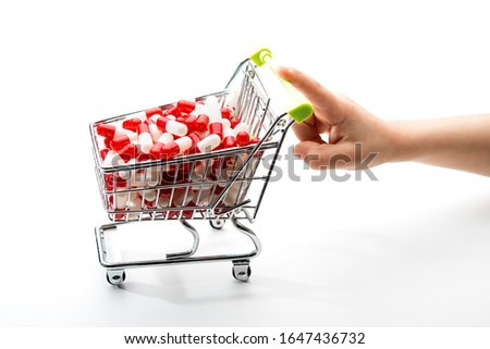 shopping cart full of medicines pushed by a child's hand, concept of addiction to the use of drugs #1647436732
