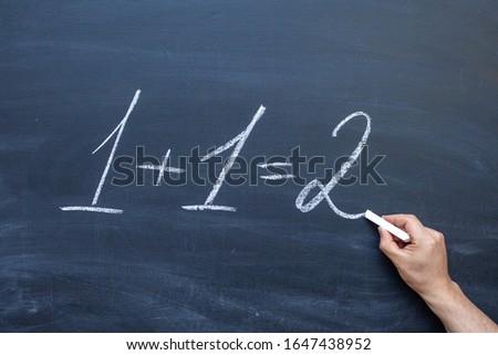 1 + 1=2 written with chalk on blackboard. One plus one equals two written on chalkboard #1647438952