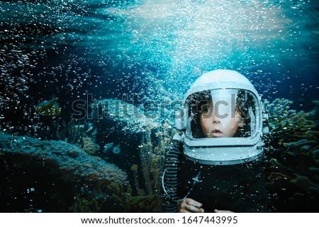 A small child dives underwater in a helmet and looks at a coral reef. Cartoon photo