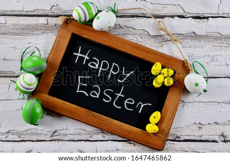 Easter greeting card. Easter eggs on the wooden board with text Happy Easter. Holiday taime and spring. Beautiful tradition.