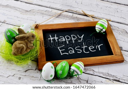 Happy easter on wooden board with easter bunny and easter eggs. Greeting card for Easter and spring time.