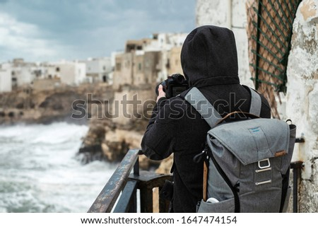Photographer taking picture of a stormy sea in Polignano a Mare, Italy