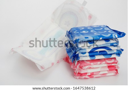 A lot of feminine sanitary pads in the package. Gaskets are stacked on top of each other. Gaskets for monthly use. Hygiene. One opened female pad. #1647538612