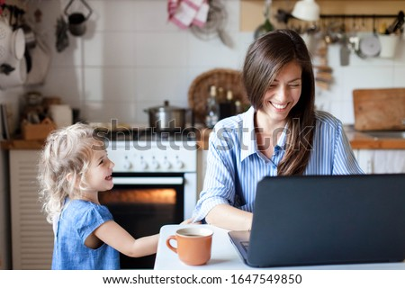 Working mom works from home office. Happy mother and daughter smiling. Successful woman and cute child using laptop. Freelancer workplace in cozy kitchen. Female business. Lifestyle authentic moment. Royalty-Free Stock Photo #1647549850