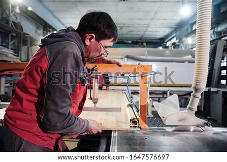 Process of production and manufacture of wooden furniture in furniture factory. Worker carpenter man in overalls processes wood on special equipment #1647576697