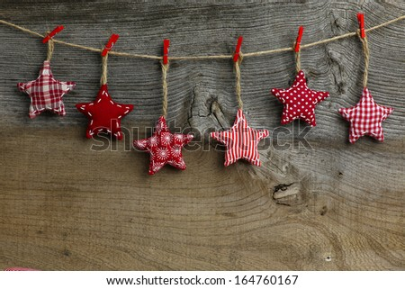 Christmas handmade decoration red and white pattern fabric stars over rustic Elm wood background - retro style design, copy space