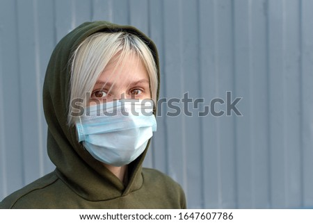 Medical mask on the girl's face. disposable medical three-layer mask with elastic. Personal protective equipment.