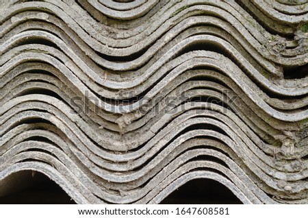 A stack of leaves of wave slate. Side view of a large number of sheets of used slate. Replacing obsolete roofing material with modern safety. Eye level shooting. Close-up. Selective focus. #1647608581