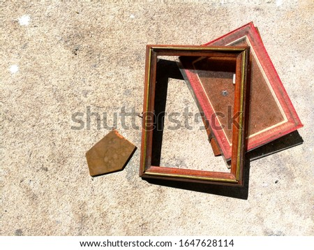 an abandon broken brown picture frame is on the concrete background