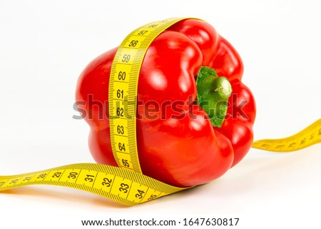 red capsicum fruit with measuring tape illustrating a healthy lifestyle isolated on white background #1647630817