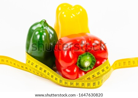 some capsicum fruits with measuring tape illustrating a healthy lifestyle isolated on white background #1647630820