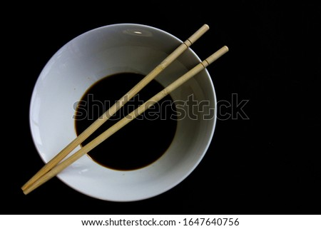 A white bowl of soy sauce and two chopsticks on a black background. #1647640756