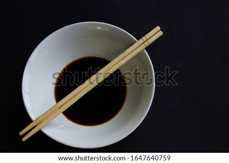 A white bowl of soy sauce and two chopsticks on a black background. #1647640759