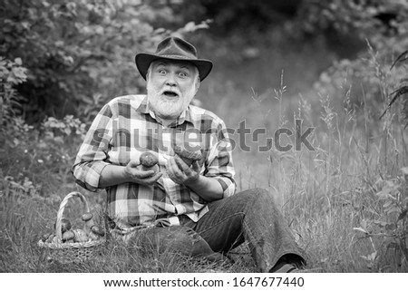 Grandfather with basket of mushrooms and a surprised facial expression. Mushrooming in forest, Grandfather hunting mushrooms over summer forest background #1647677440